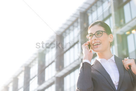 Business : Low angle view of happy businesswoman using cell phone outside office building