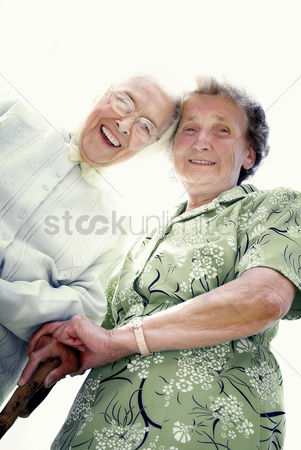 Strong : Low angle view of two old women smiling at the camera
