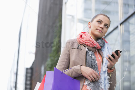Shopping : Low angle view of young woman listening to music while shopping