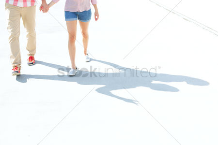 Couples : Low section of couple walking on street