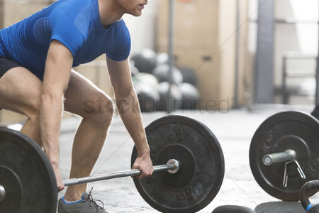 Strong : Low section of dedicated man lifting barbell in crossfit gym