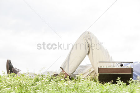 Grass background : Low section of man lying by vintage radio on grass against clear sky