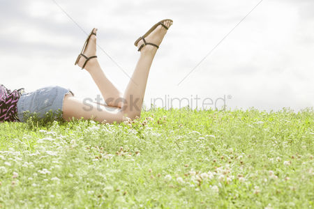 Grass : Low section of woman lying on grass against sky