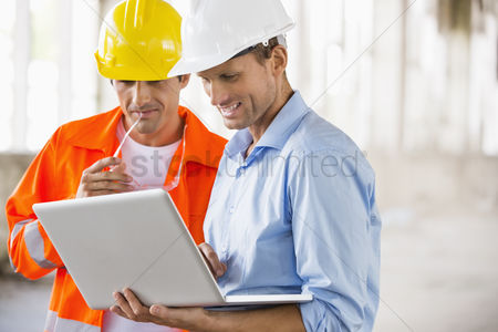 Computer : Male architects working on laptop at construction site