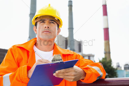 Supervisor : Male construction worker writing on clipboard at industry