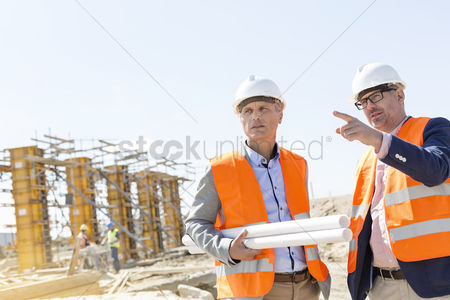 Supervisor : Male engineers discussing at construction site against clear sky