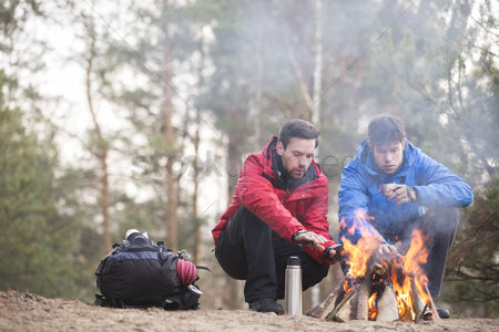 Jacket : Male hikers warming hands at campfire in forest