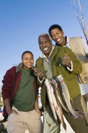 Offspring : Male members of three generation family holding fishes smiling  portrait