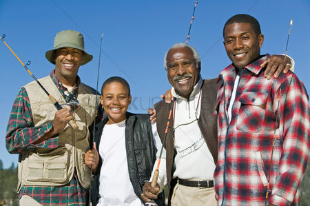 Masculinity : Male members of three generation family holding fishing rods outdoors smiling  portrait