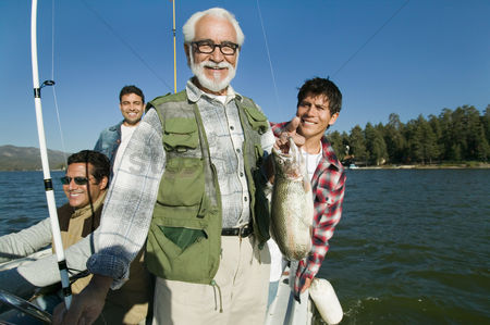 Masculinity : Male members of three generation family on fishing boat man holding fish