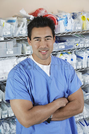 Medication : Male nurse standing by shelves with medical supply portrait