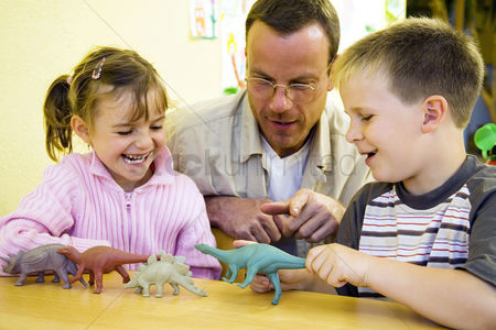 Children playing : Male teacher showing his students some dinosaur figurines