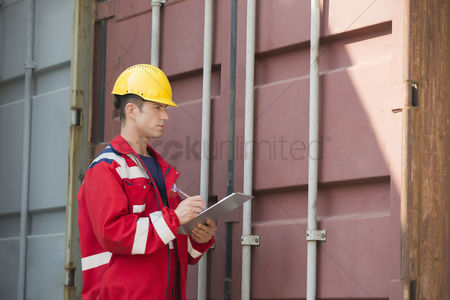 Supervisor : Male worker inspecting cargo container while writing on clipboard in shipping yard