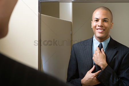 Interior : Man adjusting tie in mirror