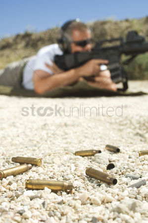 Firing : Man aiming machine gun at firing range focus on bullets in foreground