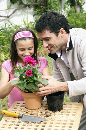 Blossom : Man and girl planting flower into a pot