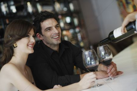 Wine bottle : Man and woman having their glasses filled up