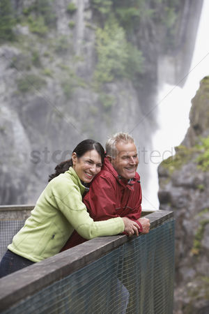 British ethnicity : Man and woman looking at view near waterfall woman embracing man