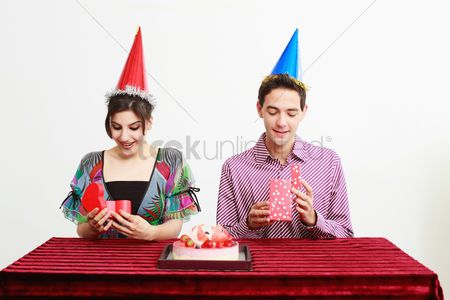 Birthday present : Man and woman opening their presents