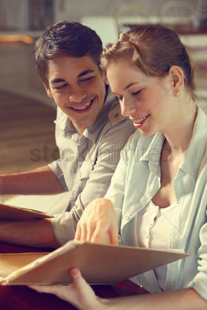 Choosing : Man and woman reading menu in a restaurant