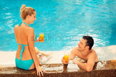 Eastern european ethnicity : Man and woman relaxing at the edge of pool with glasses of orange juice