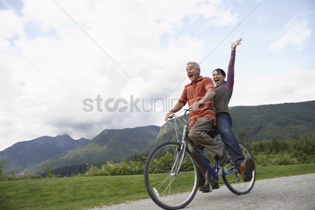 British ethnicity : Man and woman riding on one bicycle screaming
