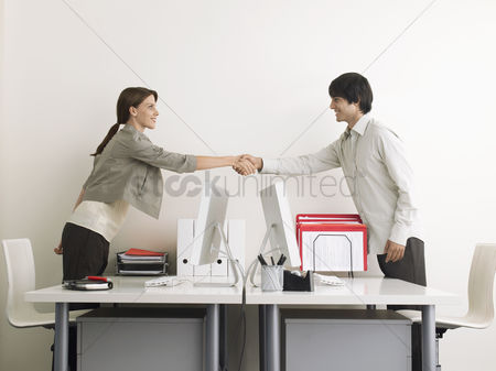Interior background : Man and woman shaking hands over desks side view