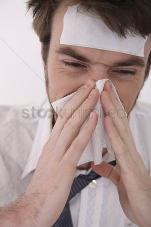 Blowing : Man blowing his nose with tissue