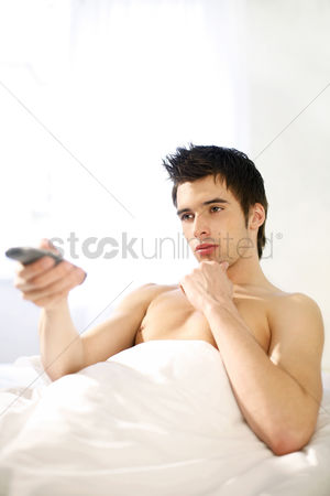 Satisfying : Man channel surfing on the bed