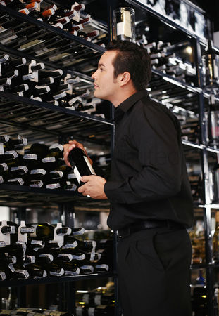 Tidy : Man choosing wine in the wine cellar