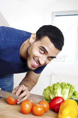 Careful : Man cutting vegetables in the kitchen