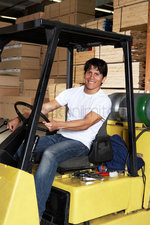 Forklift : Man driving forklift in warehouse full of wood