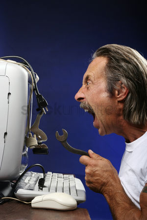 Modern lifestyle : Man getting frustrated while fixing his computer
