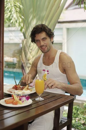 Sausage : Man having breakfast by the pool
