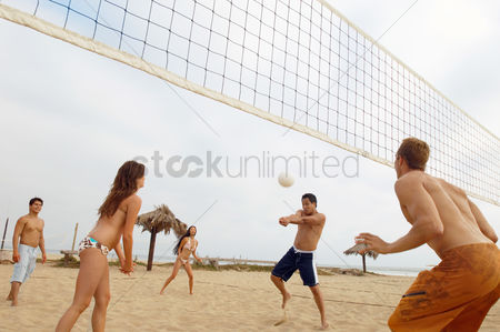 Friends : Man hitting volleyball during game on beach
