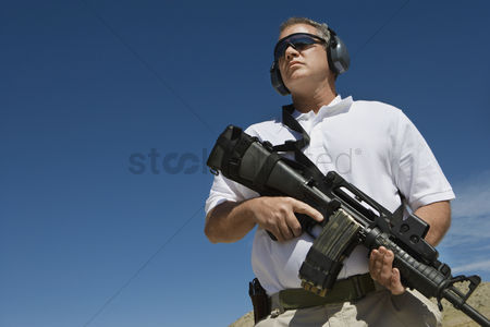 Firing : Man holding machine gun at firing range low angle view