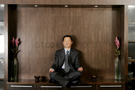Employee : Man in business suit sitting on the shelf meditating