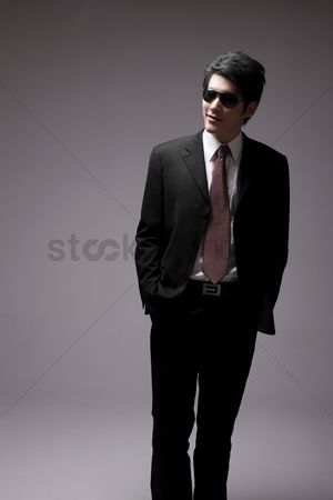 Man suit fashion : Man in full suit with sunglasses standing with his hands in pocket