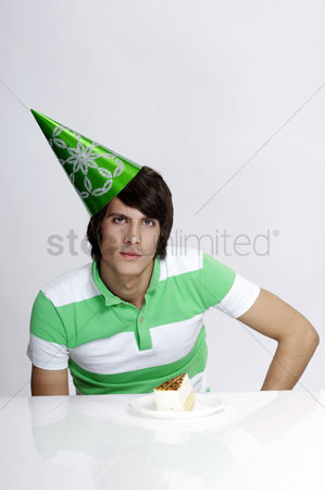 Composed : Man in party hat with a piece of cake in front of him