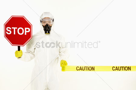 Malaysian chinese : Man in protective suit holding a  stop  sign