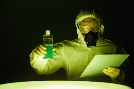Masculinity : Man in protective suit inspecting a bottle of chemical
