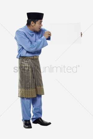 Baju melayu : Man in traditional clothing holding blank placard