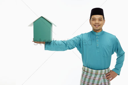 Baju melayu : Man in traditional clothing holding up a cardboard house