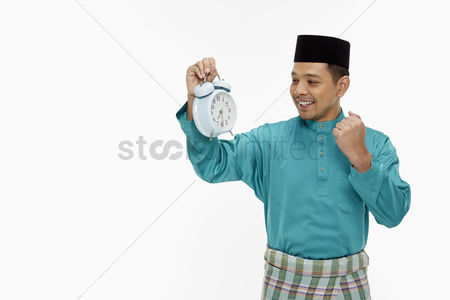 Baju melayu : Man in traditional clothing holding up a clock
