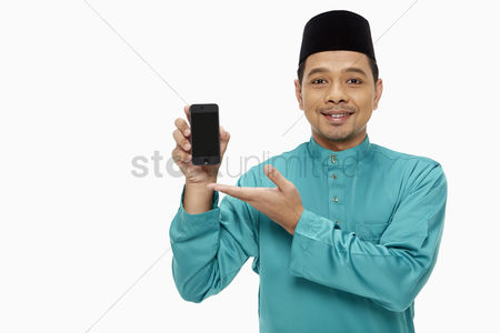 Baju melayu : Man in traditional clothing holding up a mobile phone