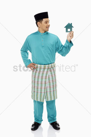 Baju melayu : Man in traditional clothing holding up a small cardboard house