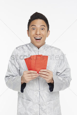 Lunar new year : Man in traditional clothing holding up red packets
