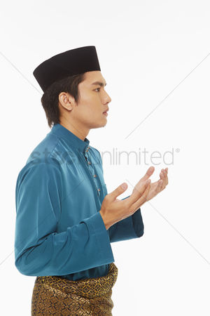 Baju melayu : Man in traditional clothing lifting up hands  praying