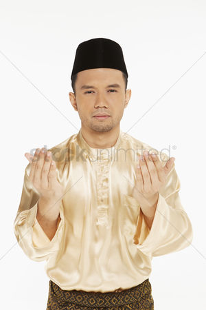 Baju melayu : Man in traditional clothing lifting up his hands  praying