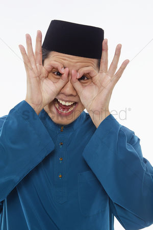Baju melayu : Man in traditional clothing making funny faces